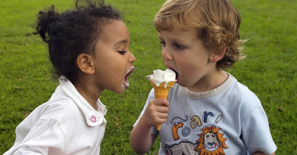 Two young children sharing an ice cream, one a blode boy the other a mixed race girl.